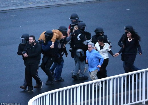Running to safety: Police escort seven hostages freed from the kosher grocers, including one woman who had to be carried