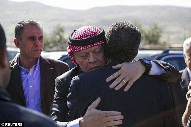 Jordan's King Abdullah II embraces Fahed al-Kasasbeh, the uncle of Jordanian pilot Moaz al-Kasasbeh