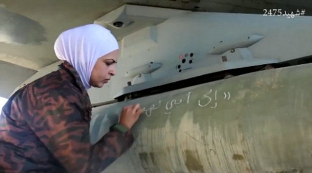 Preparation: A woman is seen writing a message in Arabic on a plane-mounted missile before the air assault