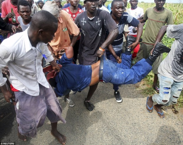 Furious Burundian protesters violently carry a female police officer they accused of opening fire on them in the capitalBujumbura