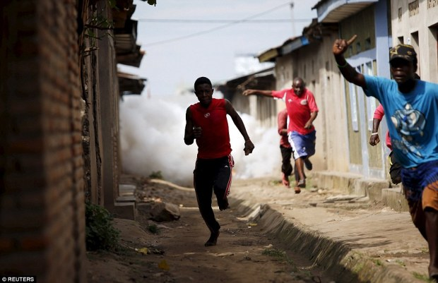 On the run: Protesters run away from police during a protest in Buterere neighbourhood of Bujumbura