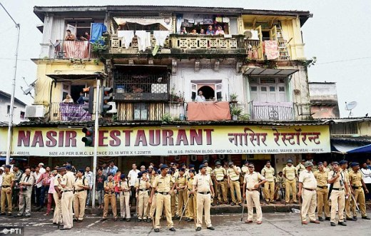 Police personnel stand guard outside Yakub's house in Mumbai