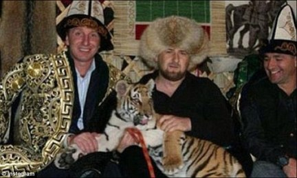 Colourful character: The former warlord (centre) seen in a bizarre social media snap cuddling a tiger which even has lead round its neck. the brutal reality of how Kadyrov maintains his grip on power has been glossed over by his social media skills and voracious appetite for posting on Instagram.