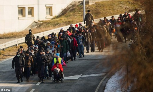 Searching for a home: Refugees   walk along a street as they cross the Slovenian-Austrian border today