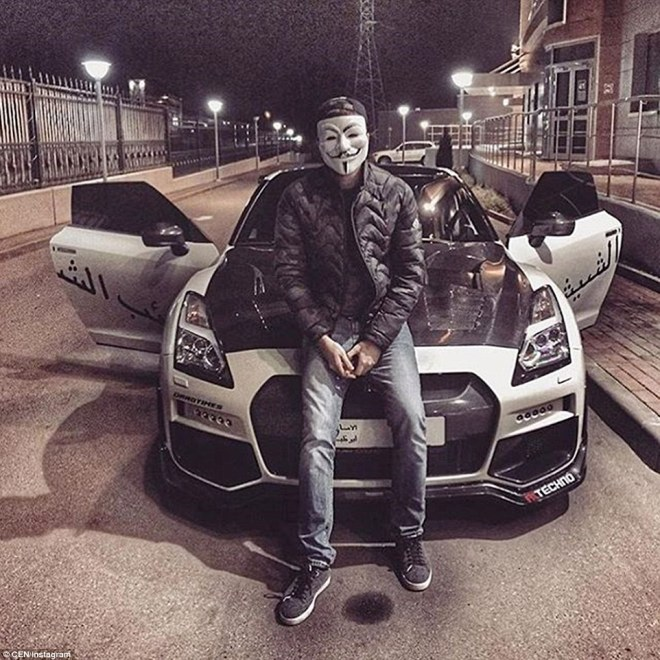 A man wearing an Anonymous mask sits on the bonnet of an expensive sports car somewhere in Russia