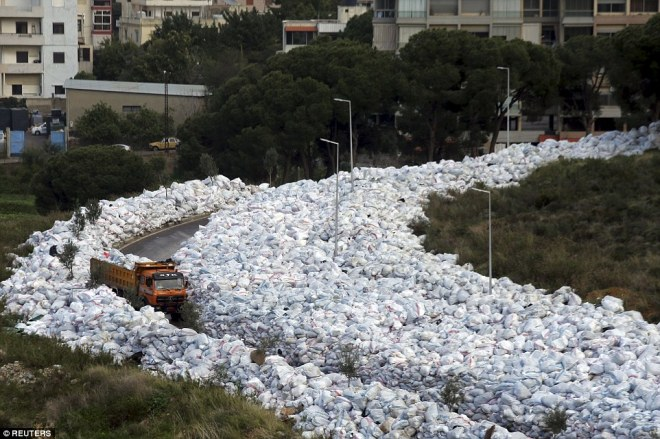 A truck drives past packed waste bags in Jdeideh, Beirut, as they line either side of the street as the rubbish crisis continues to worsen