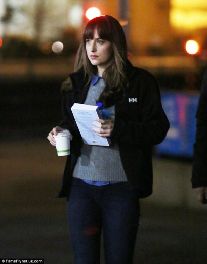 Keep it hot: On Friday actress Dakota Johnson stayed warm on the set of Fifty Shades Darker in Vancouver by wrapping up in a blue denim button-up, a grey cable-knit sweater and a black Helly Hansen fleece