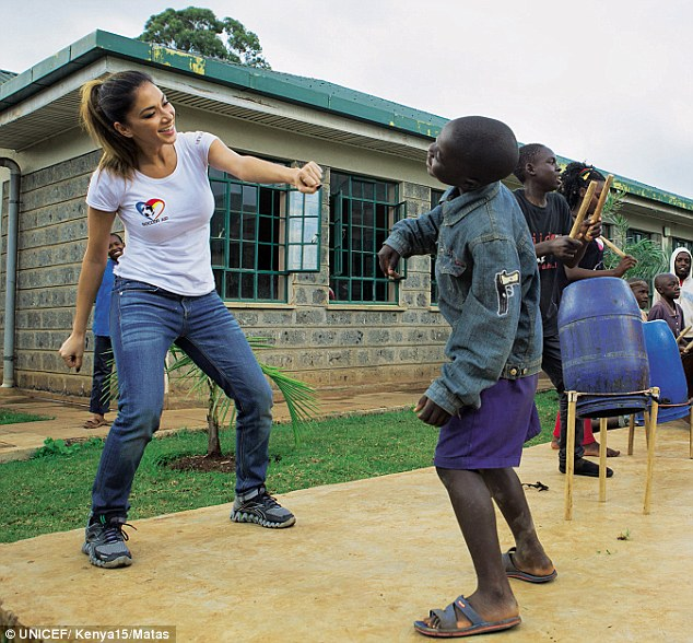 'All you can do is try to be respectful and giving, kind and loving; make them feel valued and not force yourself on them,' she said (pictured: dancing at the children's centre)