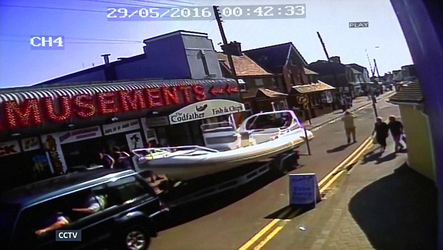 The boat was towed through Dymchurch, Kent by authorities, CCTV footage showed. Two British men were today remanded in custody charged with immigration offences