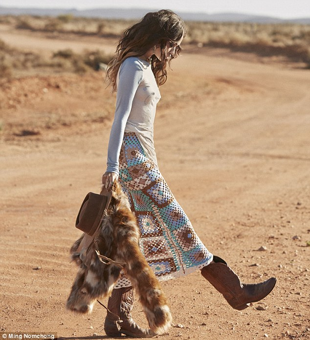 On the road: The model kicked at a dusty track while holding her sombrero and faux fur jacket