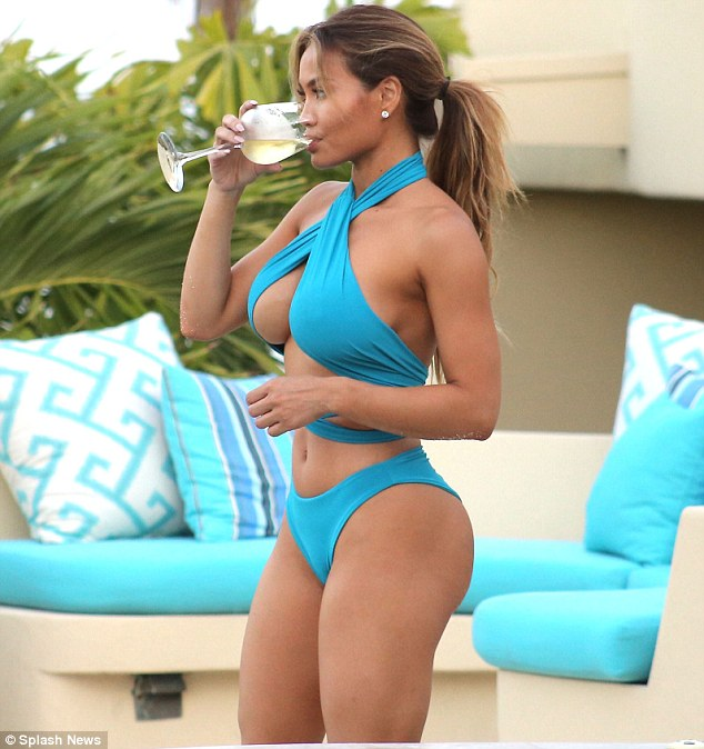 Stunning beauty: The model, who split with singer Jason Derulo in May, revealed her toned figure in the criss cross halter-style look while enjoying a beverage at the luxury resort's pool