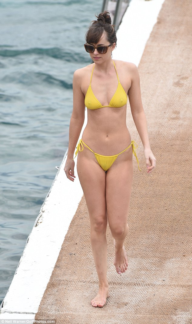 Lovely in lemon! Dakota Johnson flaunted her fabulous figure once again as she enjoyed a dip in the sea in-between filming for the movie's sequel, Fifty Shades Darker, on Tuesday