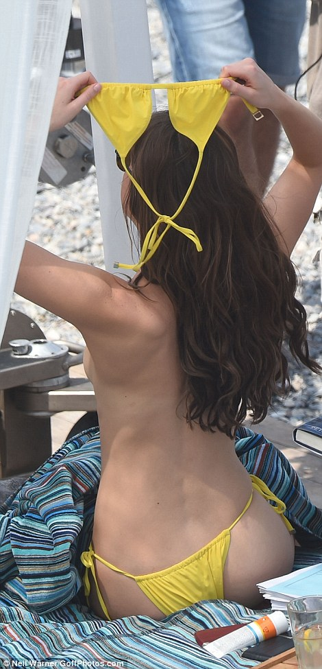 Daring to bare: The brunette beauty removed her bright yellow bikini top for the romantic moment