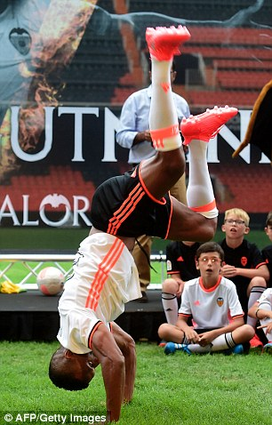 Nani shows his strength and agility as he swings his body around in a game of capoeira