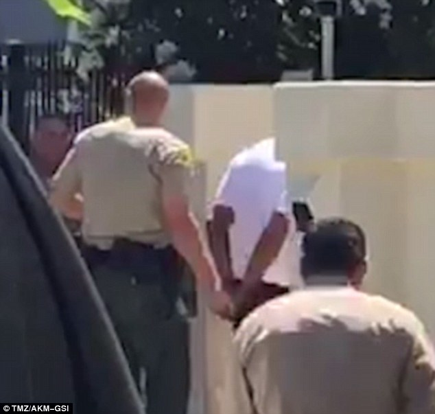 Cuffed: Dr. Dre was patted down and placed in handcuffs after sheriff's deputies responded to a 911 call from someone claiming the music mogul had pulled a gun on him during a road rage incident in Malibu on Monday