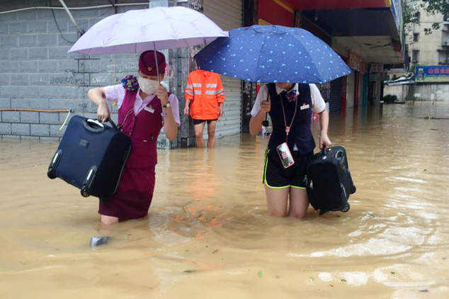 Train attendants carry their luggage as they walk through a flooded street in Fuzhou in southeastern China's Fujian Province Wednesday, Sept. 28, 2016. A mas...