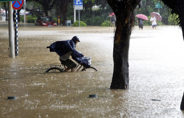 A man bicycles through a flooded street after the landfall of Typhoon Megi in Fuzhou in southeastern China's Fujian Province Wednesday, Sept. 28, 2016. A mas...