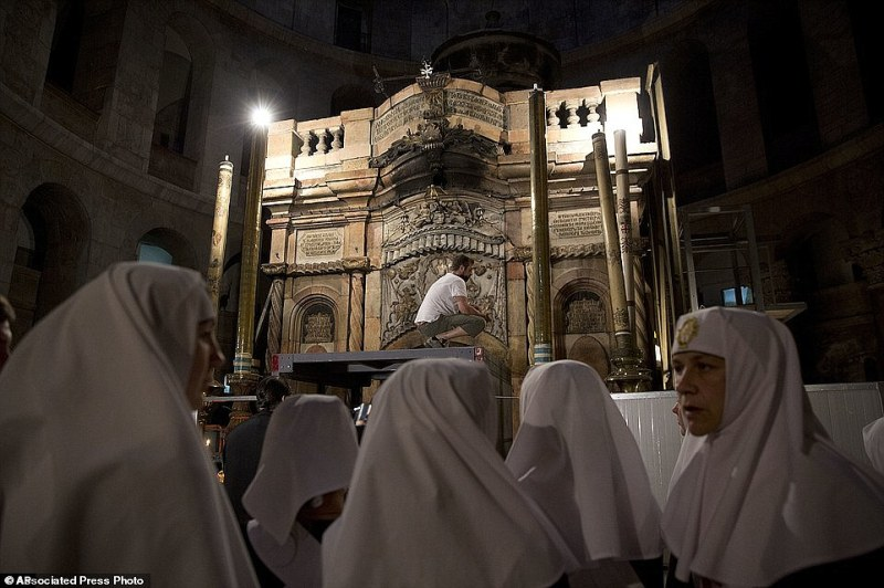 Christian nuns watch as renovations of Jesus' tomb in the Church of the Holy Sepulchre in Jerusalem's old city began earlier this year