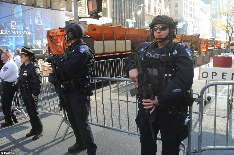 Heavily armed: Earlier in the night, heavily armed NYPD officers were seen guarding the Democratic hopeful - unaware of how thoroughly Trump would sweep many states
