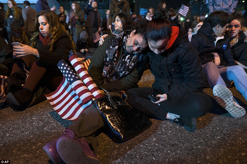 Family support: A daughter supports her mom as they slump to the ground outside the Jacob Javis Center, the home of Clinton's ultimately presumptuous election party, on Tuesday night