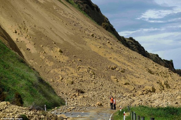Emergency services officers inspect the immense damage caused to Rotherham Road near Waiau town, 90 kilometres south of Kaikoura