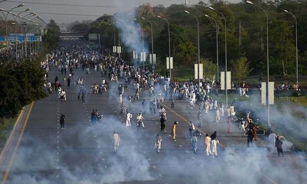Supporters of Mumtaz Qadri retreat from smoke after tear gas shelling by authorities during an anti-government protest in Islamabad on March 27, 2016.