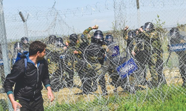 IDOMENI: Macedonian police throw stones at migrants and refugees during clashes near their makeshift camp here on Sunday.—AFP