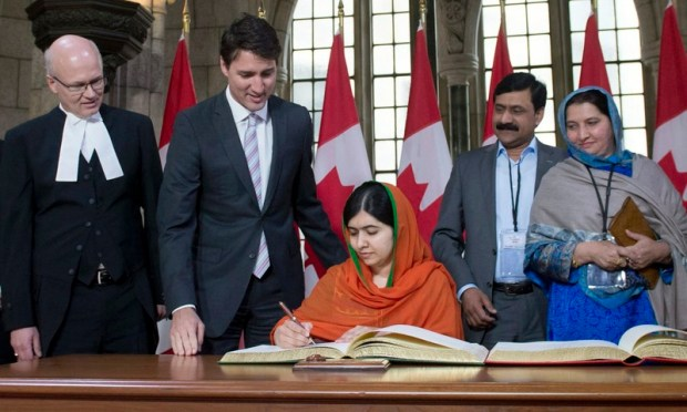 Malala Yousafzai signs the guest book as Prime Minister Justin Trudeau and Speaker of the House of Commons Geoff Regan look on. —AP