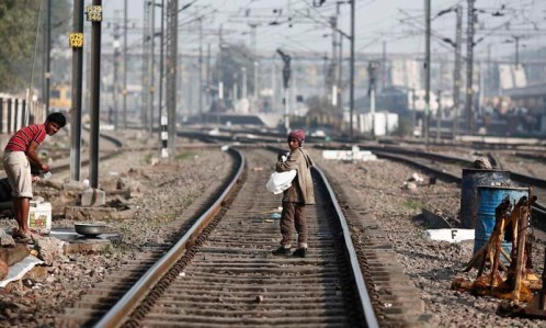 A boy walks on the tracks at a railway station in New Delhi February 18, 2014. —Reuters/File