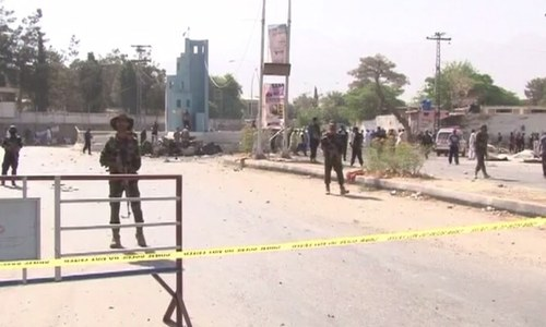 Security personnel stand-by at the site of the blast after it was cordoned off.─DawnNews
