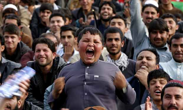 A boy goes all jubilant as crowds gather to welcome the Afghan cricket team. — AFP