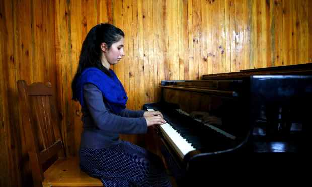 Negin Ekhpulwak, leader of the Zohra orchestra, an ensemble of 35 women, practices on a piano at Afghanistan's National Institute of Music. ─ Reuters