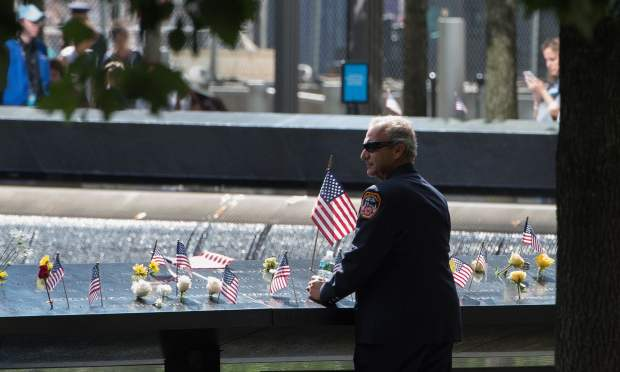 A New York City firefighter looks over the south memorial pool during the 15th Anniversary of September 11 at the 9/11 Memorial and Museum, on September 11, 2016 in New York.  — AFP