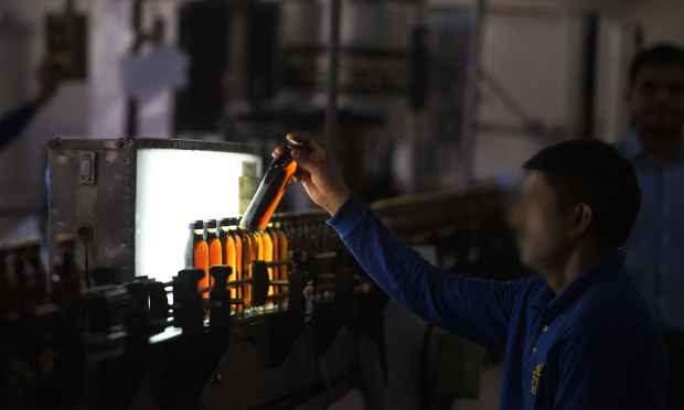 In this photograph taken on June 28, 2016, a worker scans filled whisky bottles as they pass before an illumination panel at the Muree Brewery Company in Rawalpindi. ─ AFP