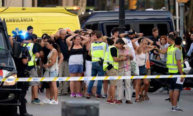 Policemen check the identity of people standing with their hands up after a van ploughed into the crowd. —AFP