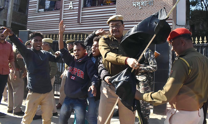 Assam Police personnel remove black flags from Krishak Mukti Sangram Samiti (KMSS) activists protesting with 69 other indigenous organisations of Assam during a demonstration against the Citizenship Amendment Bill 2016. — AFP