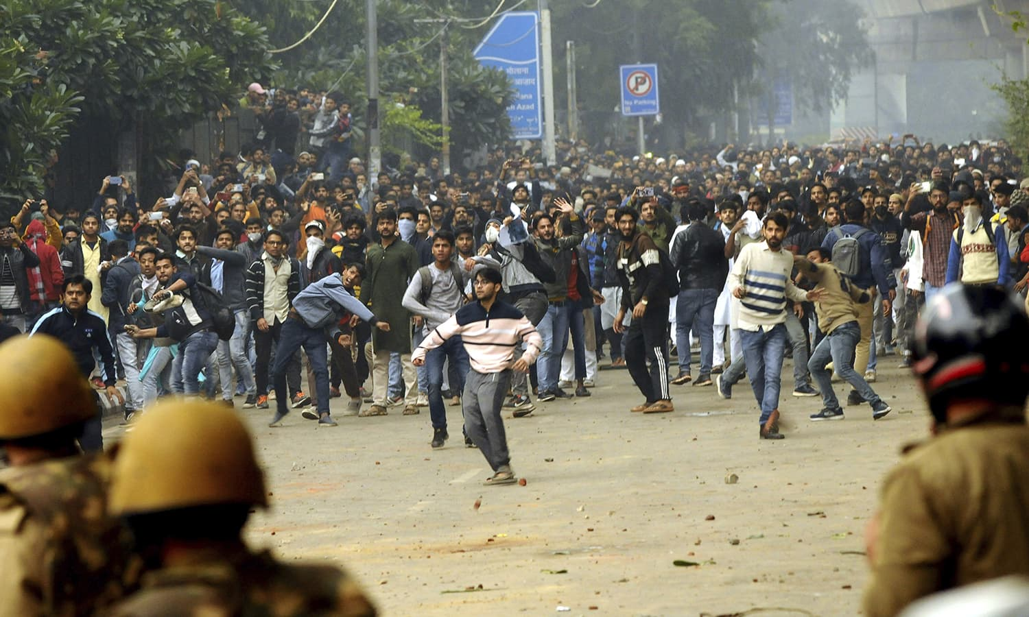 Students shout slogans and pelt stones outside the Jamia Millia Islamia University during a protest against the Citizenship Amendment Bill, in New Delhi, India, Friday. — AP