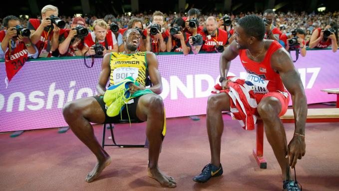 Usain Bolt of Jamaica (L) sits on a bench with Justin Gatlin of U.S. after the men's 200 metres final during the 15th IAAF World Championships