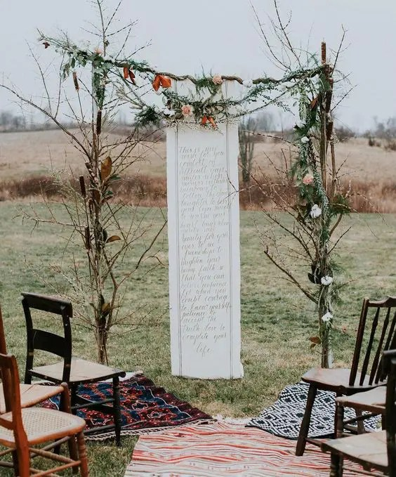 branch wedding arch with leaves and a quote backdrop