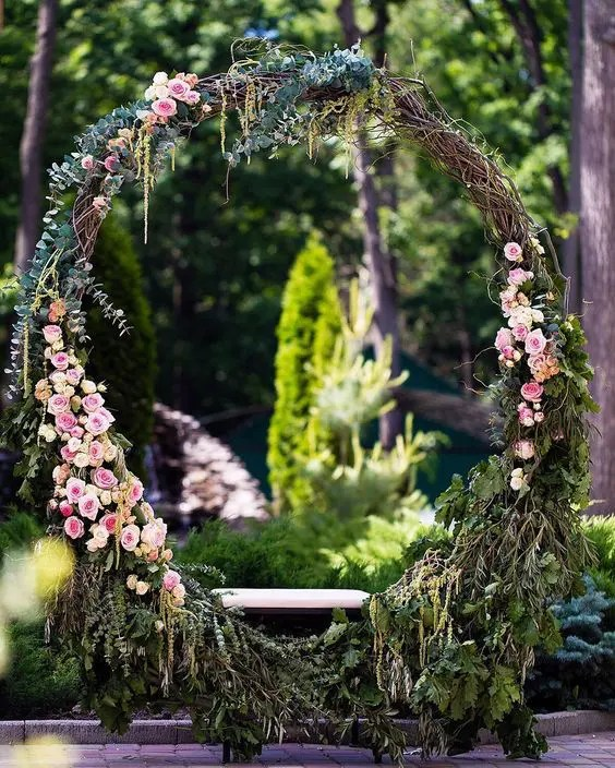 oversized grapevine wreath with pink flowers, eucalyptus and a swing seat