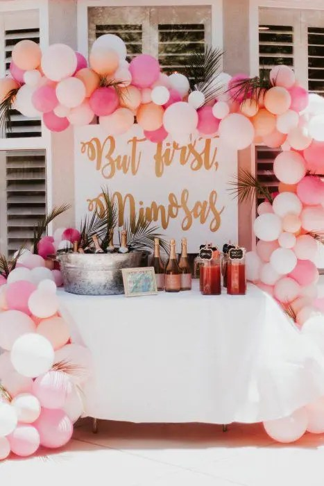 pink and peachy mimosa bar with lots of pink champagne bottles