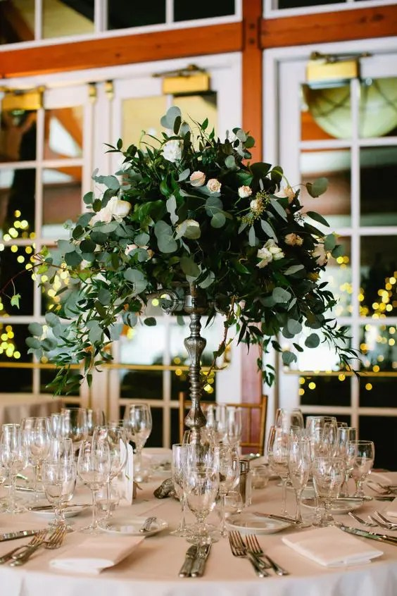 a eucalyptus and small blush roses centerpiece on a tall stand looks very elegant and chic