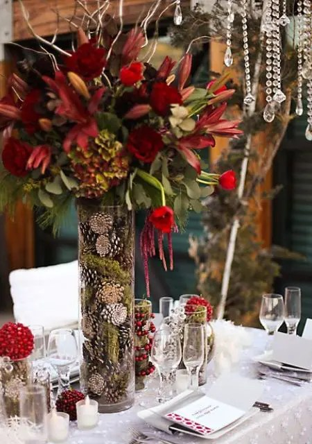 a tall vase filled with moss and pinecones and with red blooms brings a winter feel