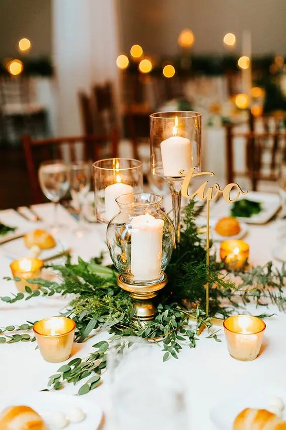 a chic greenery centerpiece with threee candles in candle holders and some candles around