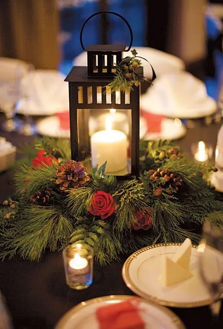 a candle lantern with a wreathof evergreens, red roses and pinecones for a rustic celebration