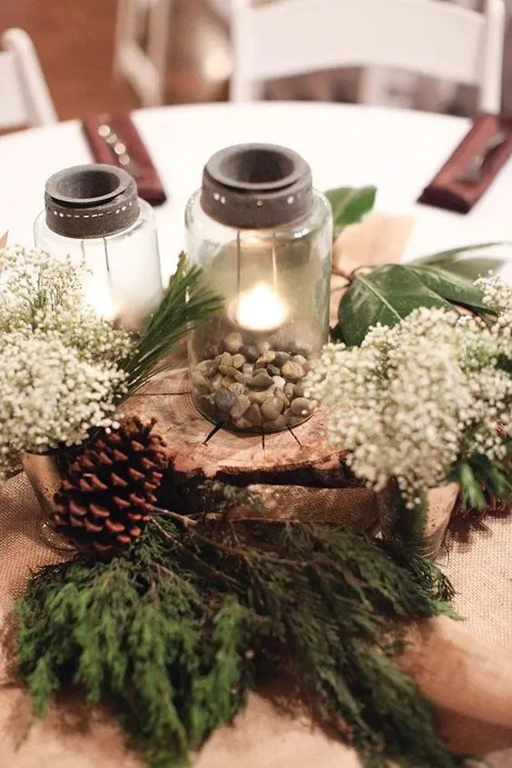 a rustic wedding centerpiece with mason jars, pebbles, a wood slice, evergreens, baby's breath