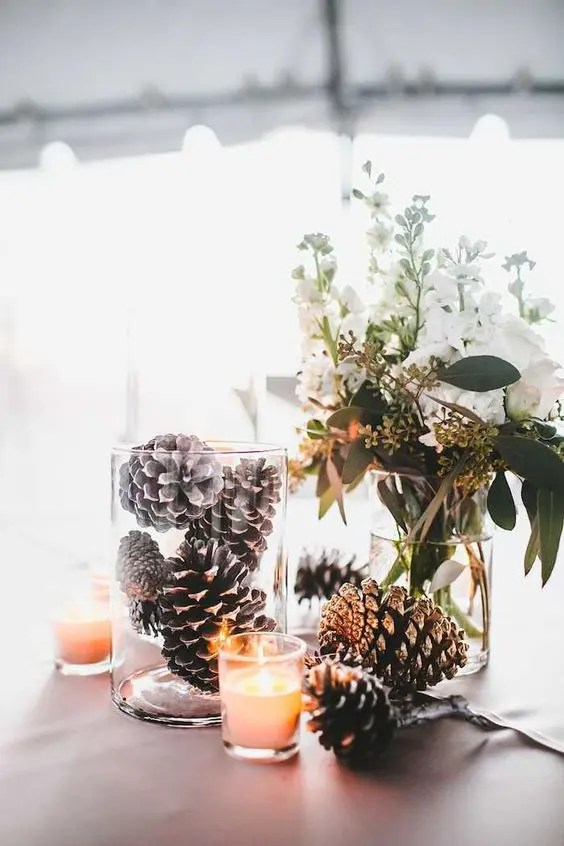 a centerpiece with some white blooms, snowy pinecones in a jar and a candle