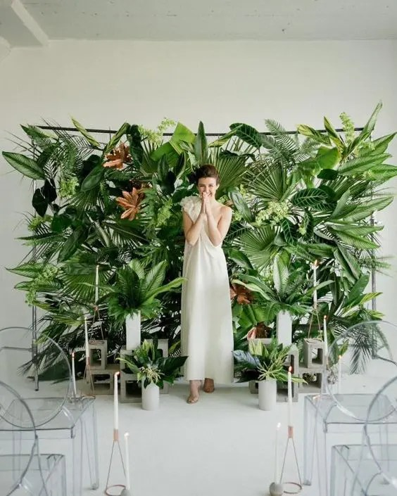 a lush tropical leaf wall and leaves in concrete vases create bold modern tropical decor