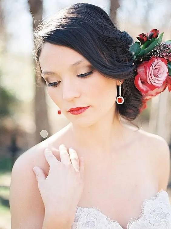 statement red stone earrings match the red lips and flowers in the bride's hair