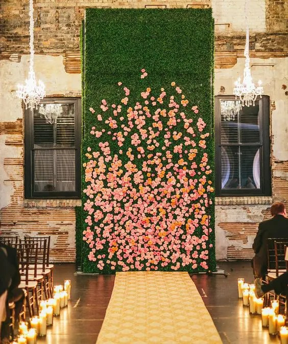 a living wall with real orange and pink blooms and a couple of glam chandeliers completely changes the venue
